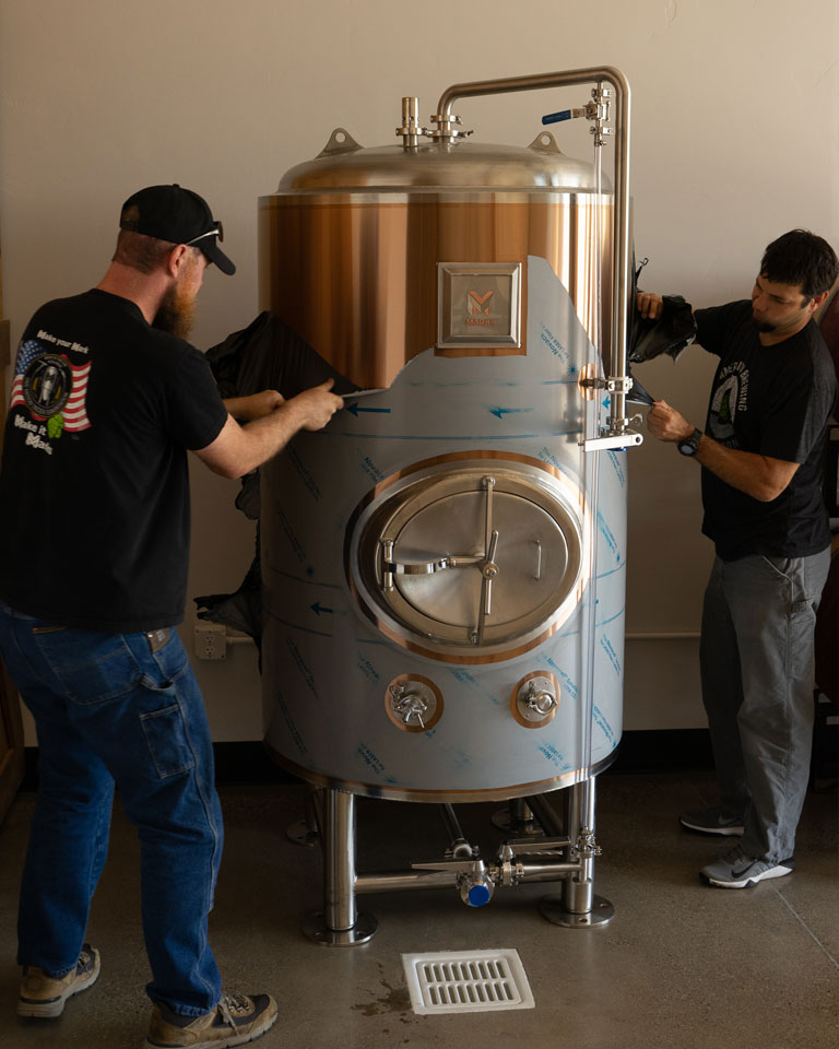 MARKS' crew peels off the protective tape from a new tank after setting up in a brewery.