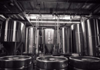 Kegs standing in front of MARKS made steel brewing tanks.