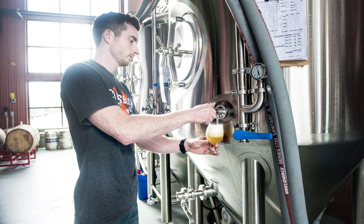 Steven from MARKS Design and Metal Work tests a beer from a stainless steel vault.